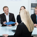 Job applicant handing over her curriculum vitae young blond female sitting with back to the camera to a smiling businessman Stock Images