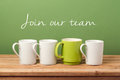 Job recruit concept with coffee cups and text `Join our team`. Business background