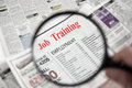 Job training magnifying glass over a newspaper classified section with text Royalty Free Stock Image