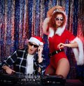 Jockey girl dj men mixing up some christmas cheer with attractive snow maiden disco lights in the background Stock Photos