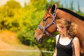 Jockey young girl petting and hugging brown horse Royalty Free Stock Photo