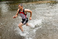 Jogger running through a streambed Stock Images