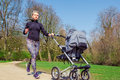 Jogging with a baby buggy young mother Royalty Free Stock Images