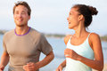 Jogging fitness young people running happy smiling mixed race couple and laughing enjoying sports outdoors exercising Stock Images