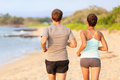 Jogging running couple on beach view from behind young fitness sand relaxed training outdoor in summer sunset Royalty Free Stock Photos