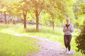 Jogging sport concept young running fitness woman training outd outdoor in the forest while listening to music horizontal image Royalty Free Stock Photos