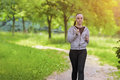 Jogging sport concept young running fitness woman training outd outdoor in the forest while listening to music horizontal image Royalty Free Stock Photography