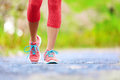 Jogging woman with athletic legs and running shoes female walking on trail in forest in healthy lifestyle concept close up on Royalty Free Stock Photo