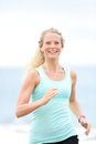 Jogging woman running woman outside on beach female fitness runner girl jogger training outdoors listening to music in earphones Royalty Free Stock Photos