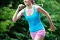 Jogging young pretty woman in the green park Stock Images