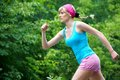 Jogging young pretty woman in the green park Royalty Free Stock Photos