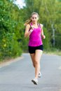 Jogging young sports girl is running in park Stock Image