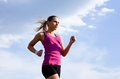 Jogging young sports girl runs on a background of blue sky Royalty Free Stock Images