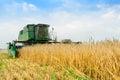 John Deere Combine Harvester Harvesting Wheat in the Field. Royalty Free Stock Photo