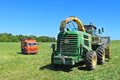 The John Deere 7450 forage harvester and the KamAZ truck Royalty Free Stock Photo