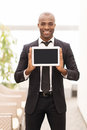 Join a digital age cheerful young african man in formalwear showing screen of tablet and smiling at camera Stock Image