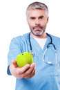 Join healthy lifestyle confident mature surgeon in blue uniform stretching out a green apple while standing isolated on white Royalty Free Stock Photos