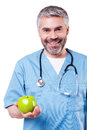 Join healthy lifestyle happy mature surgeon in blue uniform holding green apple and smiling while standing isolated on white Royalty Free Stock Photography
