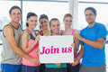 Join us against modern blue and white room the word portrait of a group of fitness class holding blank paper Royalty Free Stock Images