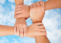 Joined hands in a symbol of cooperation on sky with clouds Stock Photo