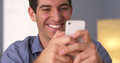 Jolly man texting on smartphone a at home Royalty Free Stock Photo