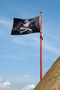 Jolly roger pirate flag with a skull and crossbones on a blue sky background Royalty Free Stock Photos