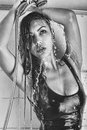 Jong meisje die in t shirt met open schouders een douche zwarte witte foto water geven Stock Fotografie