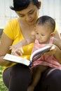 Jonge moederlezing terwijl baby-sitting Royalty-vrije Stock Foto's