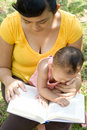 Jonge moederlezing terwijl baby-sitting Stock Foto