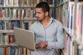 Jonge student using his laptop in een bibliotheek Stock Fotografie