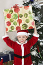 Jongen in santa claus outfit carrying present on hoofd Stock Foto