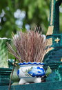 Joss sticks jar burned in a white ceramic vase with traditional thai chinese paint style in front af a small spirit house in Royalty Free Stock Images