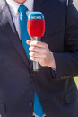 Journalist with microphone reporting news Royalty Free Stock Images