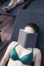 Jovem mulher em um roupa de banho que encontra se para baixo e que relaxa com um livro sobre sua cara Foto de Stock