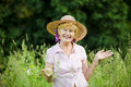 Joy friendly happy mature woman in straw hut with stretched arms smiling old lady cup meadow Stock Photo