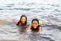 Joy inside the water two beautiful asian girls enjoying swim with a smile Royalty Free Stock Photography