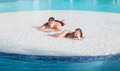 Joyful beautiful smiling little girl and teenage boy relaxing in swimming pool island on summer beautiful gorgeous day