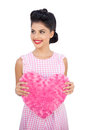 Joyful black hair model holding a pink heart shaped pillow Royalty Free Stock Photo