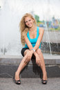 Joyful blond woman sitting near the fountain Royalty Free Stock Photos