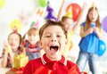 Joyful boy looking at camera with his friends on background Royalty Free Stock Image