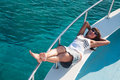 Joyful brunette woman laying on yacht deck shipboard of copyspace Royalty Free Stock Photo