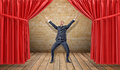 A joyful businessman standing at a wooden stage between red curtains in a victory pose. Royalty Free Stock Photo