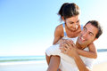 Joyful couple fooling around on thebeach man carrying girlfriend his back at the beach Stock Photo