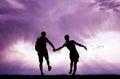 Joyful couple hand to hand at sunset
