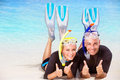 Joyful diver couple lying down on the beach wearing mask and flippers for snorkeling gesturing by hands good mood active summer Stock Image