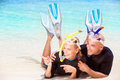 Joyful diver couple lying down on the beach wearing mask and flippers for snorkeling looking on the side and showing on something Royalty Free Stock Photography