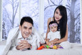 Joyful family on bed in winter day portrait of little happy enjoy holiday at home with background the window Royalty Free Stock Photography