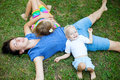 Joyful family enjoying themselves laying on the grass Stock Images