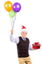 Joyful gentleman holding gift and balloons Stock Photo