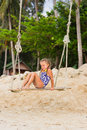 Joyful girl in a bathing suit on a swing with two braids swimsuit sits the beach Royalty Free Stock Image
